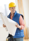Architect Looking Away While Holding Blueprint At Construction S — Stock Photo