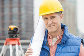 Portrait Of Confident Architect Holding Rolled Up Blueprint — Stock Photo