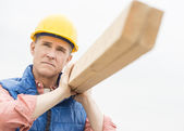 Thoughtful Worker Carrying Wooden Plank — Stock Photo