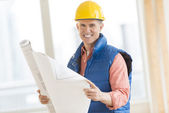 Happy Construction Worker Holding Blueprint At Site — Stock Photo