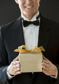 Midsection Of Happy Man In Tuxedo Holding Gift Box — Zdjęcie stockowe