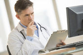 Serious Doctor Looking At Computer While Holding Clipboard At De — Stock Photo