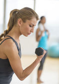 Woman Lifting Dumbbell At Health Club — Stock Photo
