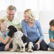 Happy Girl Playing With Dog While Family Looking At Her — Stockfoto