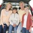 Happy Family Of Four Sitting In Car Trunk — Photo