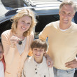 Woman Showing Keys While Standing With Family Against Car — Stock Photo