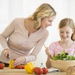Stock Photo: Girl Assisting Mother In Preparing Food At Counter