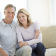 Happy Couple Sitting On Sofa In Living Room — Stock Photo