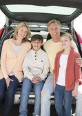 Gelukkige familie van vier zitten in auto kofferbak — Stockfoto