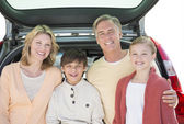 Parents And Children Standing In Front Of Open Car Trunk — Stock Photo