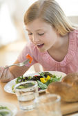 Girl Eating Salad At Dining Table — Stock Photo