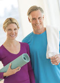 Couple With Water Bottle Exercise Mat And Towel In Gym — Stock Photo