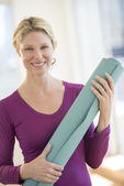 Happy Woman Holding Exercise Mat In Health Club — Stock Photo