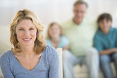Woman With Family Sitting On Sofa In Background At Home — Stock Photo