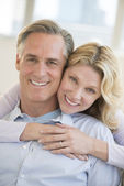 Happy Woman Embracing Man From Behind At Home — Stock Photo