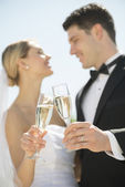 Couple Toasting Champagne Flutes Against Sky — Stock Photo