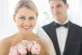 Bride With Bouquet Of Roses While Groom Standing In Background — Stock Photo