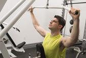 Człowieka, ćwiczenia z koła pasowego w siłowni — Zdjęcie stockowe