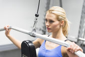 Woman Looking Away While Doing Weight Exercise At Club — Stock Photo