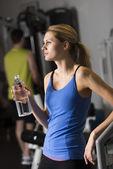 žena s láhev s vodou koukal v tělocvičně — Stock fotografie