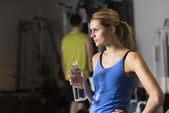 Woman With Bottle Of Water Looking Away At Gym — Stock Photo