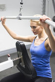 Woman Exercising On Pulley At Gym — Stock Photo