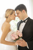Bride And Groom With Flower Bouquet Rubbing Noses — Stock Photo