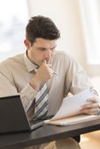 Businessman Looking At Documents While Sitting At Desk In Office — Stock Photo