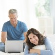 Woman Relaxing In Bed While Man Using Laptop — Stock Photo