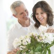 Foto Stock: Happy Couple Arranging Flowers
