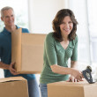 Beautiful Woman Packing Cardboard Box At Home — Stock Photo #30514919