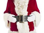 Midsection jultomten med händerna på magen — Stockfoto