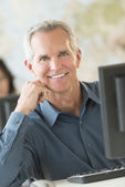 Happy Businessman Leaning At Computer Desk — Stock Photo
