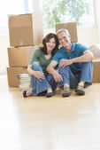 Mature Couple Sitting Together On Floor In New House — Stock Photo