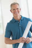 Happy Man Holding Blueprint In New House — Stock Photo