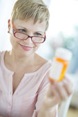 Woman Looking At Pill Bottle — Stockfoto