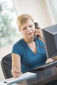 Kobieta przy użyciu telefonu stacjonarnego podczas pracy przy biurku — Zdjęcie stockowe