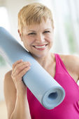 Woman Holding Rolled Up Exercise Mat At Gym — Stock Photo