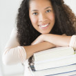 Girl Smiling While Leaning On Stacked Books In Classroom — Stock Photo