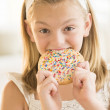 Girl Eating Cookie With Sprinkles On It At Home — Stock Photo