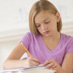 flicka skriva noter i bok vid skrivbord — Stockfoto