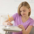 Schoolgirl Writing Notes In Book At Classroom — Stock Photo