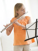 Girl Playing Flute At Home — Stock Photo