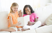 Friends Reading Book On Sofa At Home — Stock Photo