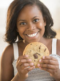 Girl Holding Chocolate Chip Cookie At Home — Stock Photo