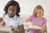 Schoolgirls Writing Notes At Desk — Stock Photo