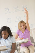 Schoolgirl Raising Hand To Answer In Classroom — Stock Photo