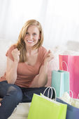 Woman Clenching Fists With Shopping Bags On Sofa — Stock Photo
