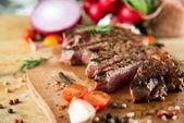Baharat ve sebzeler ile pişmiş sığır eti biftek — Stok fotoğraf