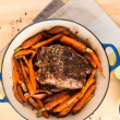 oven roasted pork shoulder in enameled pan with carrots and sweet potatoes — Stock Photo